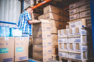 Lagermitarbeiter überprüft Lieferung mit Produkten von TENA vor Regal im Lager von MEDiHandel