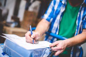 Lagermitarbeiter überprüft Lieferung mit Produkten von TENA im Lager von MEDiHandel