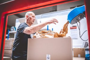 Lagermitarbeiter verpackt medizinische Produkte in Kartons im Lager von MEDiHandel