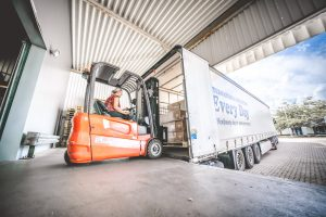 Orange Gabelstapler entleert LKW am Lager von MEDiHandel
